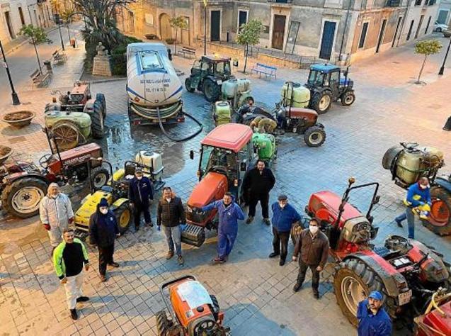 Tractors bleaching streets of Santa Maria del Cami, Majorca