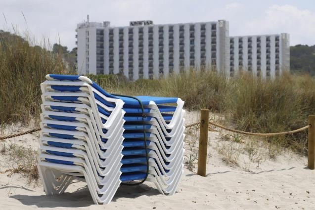 Menorca sunloungers stacked on a beach