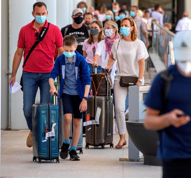People wear protective face masks as they make their way