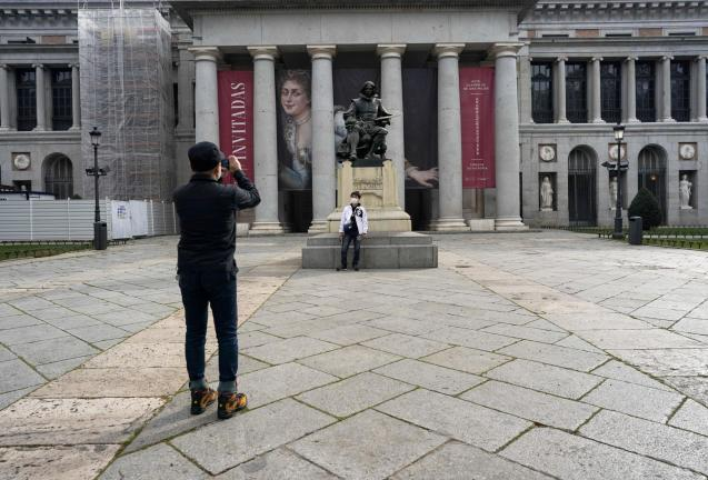: A man wearing a protective mask takes a photo in front of El Prado museum in Madrid