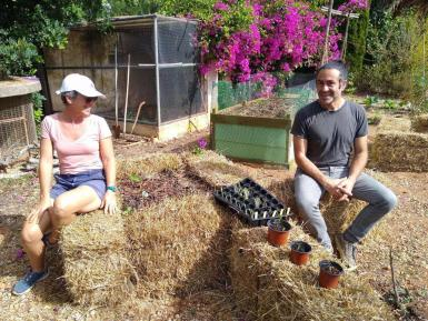 Heather and Joe sitting on one of the straw beds in the kitchen garden with the first of the Hugelkultur beds in the background.