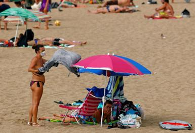 A woman wearing a protective mask is seen on the beach as the regional government of the Canary Islands forbids smoking without maintaining a safe distance and makes mandatory to wear protective masks in open public spaces, during the spread of the coronavirus disease (COVID-19) pandemic, in Las Palmas de Gran Canaria, Gran Canaria, Spain.