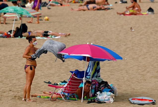 A woman wearing a protective mask is seen on the beach