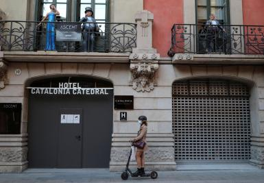 A woman rides a scooter past a closed hotel at Barrio Gotico (Gothic Quarter), after Catalonia's government imposed new restrictions in an effort to control the spread of the coronavirus disease (COVID-19), in Barcelona.