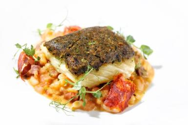 Fillet of cod in a black olive crust with chorizo and white beans.