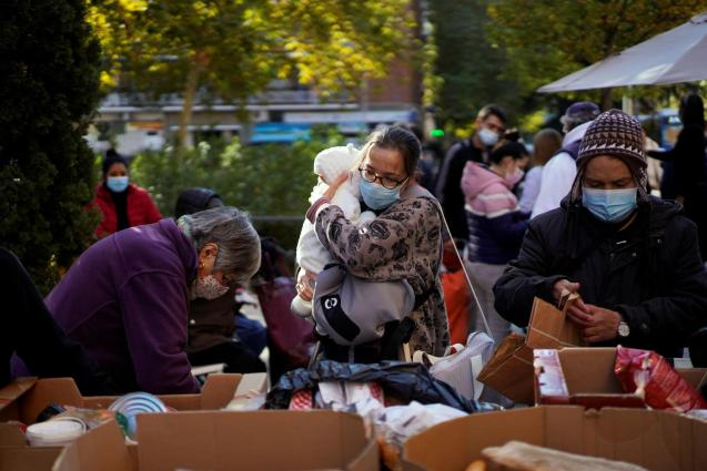 Members of NGO Madrina Foundation serve vulnerable people by distributing food, in Madrid
