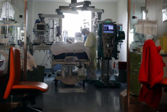 A medical worker takes care of a patient infected with COVID-19 at the intensive care unit (ICU) of Ramon y Cajal hospital in Madrid