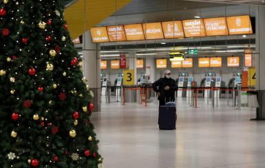 A passenger stands in an almost empty check-in area at Gatwick Airport, amid the coronavirus disease (COVID-19) outbreak, in Crawley in this file photo.