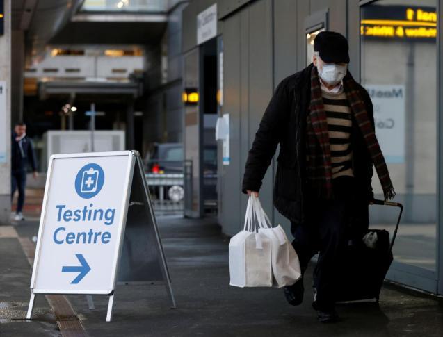 A passenger walks past a testing centre