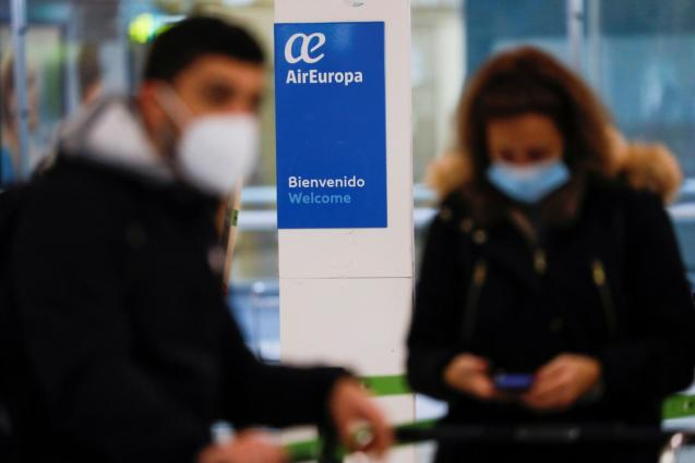Passengers wearing facemasks wait to check-in at an Air Europa counter at Adolfo Suarez Barajas airport amid the coronavirus disease (COVID-19) pandemic in Madrid
