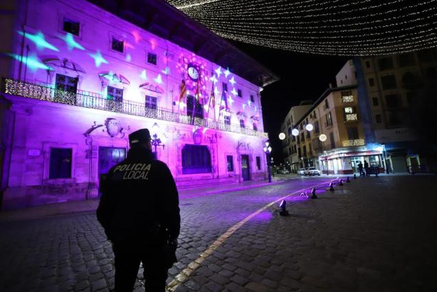 A police officer in an empty town hall square in Palma on New Year's Eve