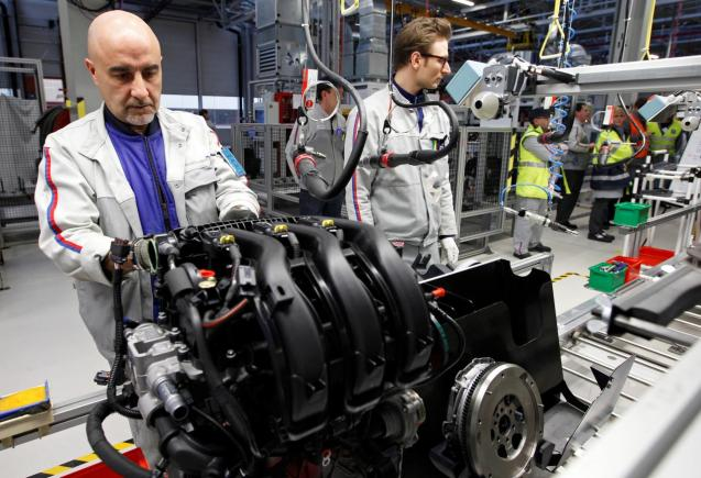 Employees of French carmaker PSA Peugeot Citroen work on the new engine