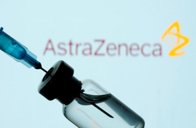 Vial and sryinge are seen in front of displayed AstraZeneca logo