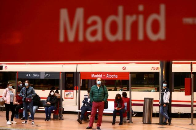 Commuters wearing protective face masks wait on a platform at Atocha train station in Madrid