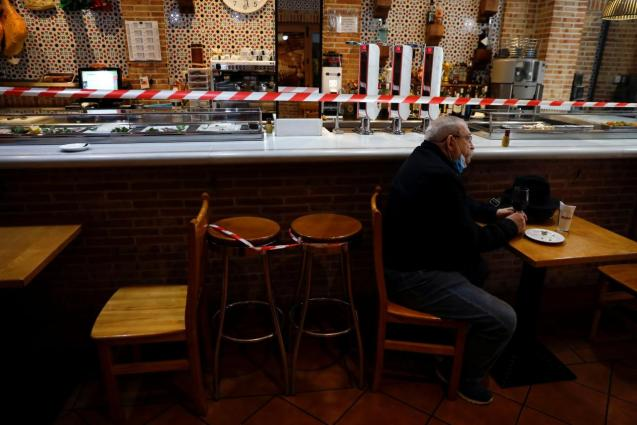 """Man sits by a cordoned off bar counter at """"Dominguez"""" restaurant in Madrid"""