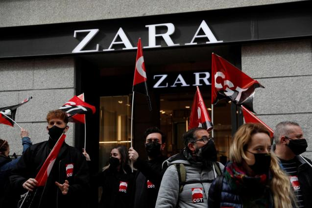 People hold flags from Spain's CGT labour union as they protest outside a Zara clothing store in Madrid