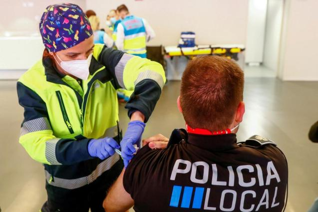 A police officer receives his first dose of the AstraZeneca COVID-19 vaccine in Madrid
