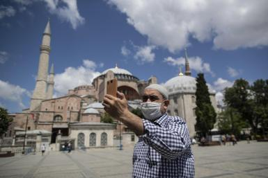 A man wearing protective face mask takes selfie in front of the Hagia Sophia museum in Istanbul.