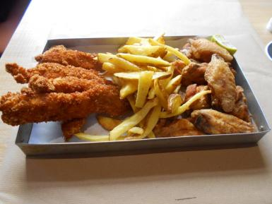 Breaded chicken fingers, deep-fried chicken wings and chips as served at Buco Burger in a traditional llauna.
