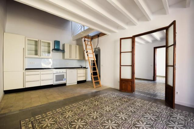 A practical kitchen with good work surfaces and a wonderful light from the home's French balconies