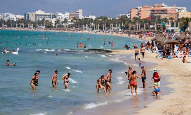People sunbathe and swim on El Arenal beach.