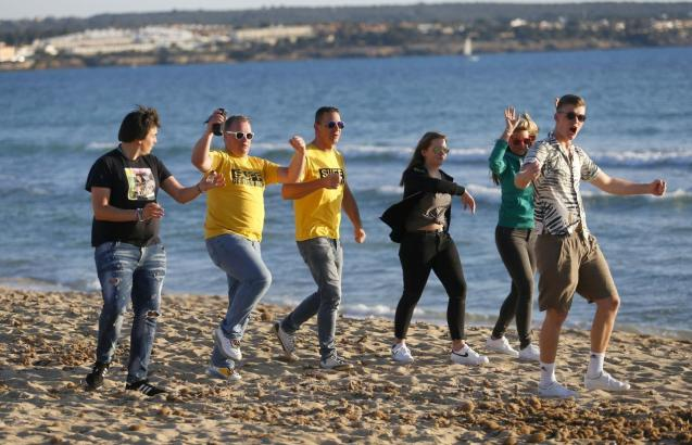 Tourists from Germany dance at El Arenal beach in Palma de Mallorca