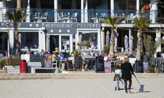 Tourists chill and take drinks in terrace bars in Paguera beach