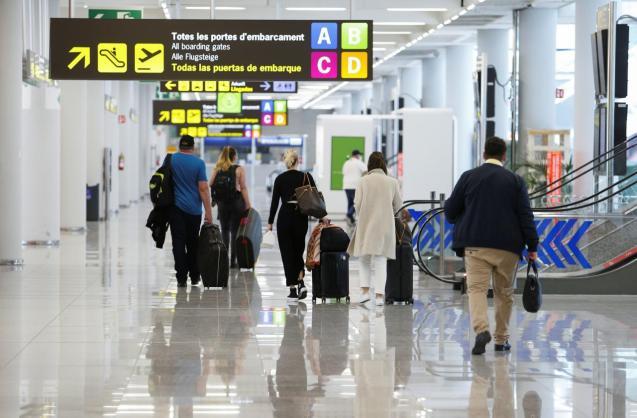 People walk towards departure doors at Son Sant Joan airport in Palma de Mallorca