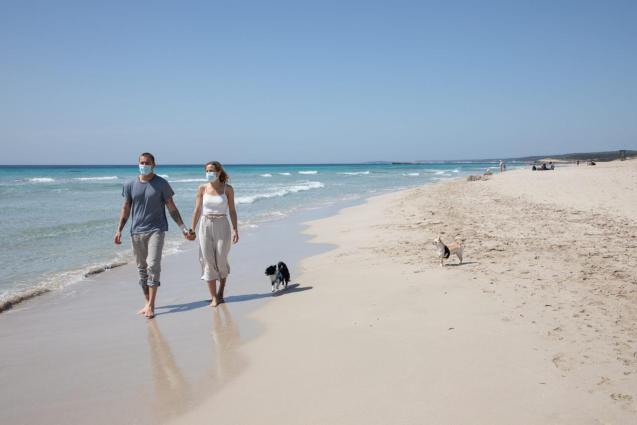 A couple walk on a beach in Menorca