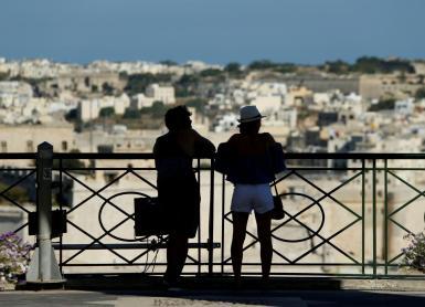 Tourists at Upper Barrakka Gardens admire the view of Grand Harbour in Valletta, Malta.