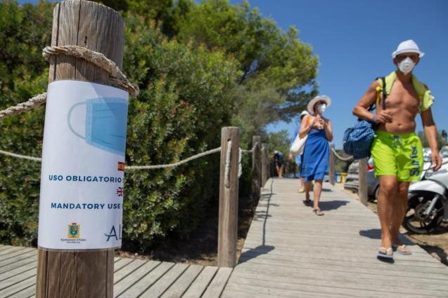 Beachgoers in Menorca with masks