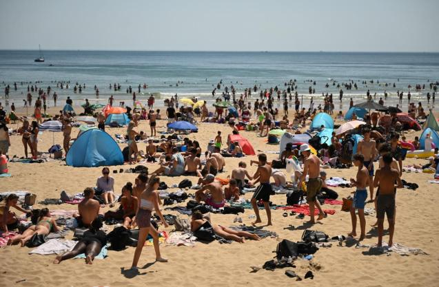 People gather on the beach and seafront on a hot day in Bournemouth