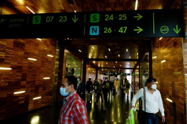 Passengers wearing protective face masks walk at Lisbon's airport
