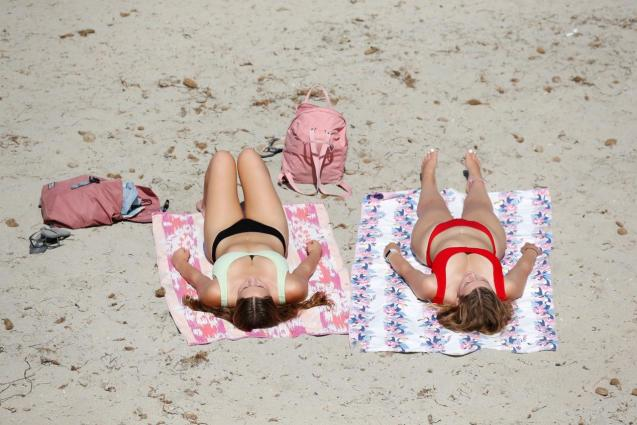People sunbathe on a sandy beach