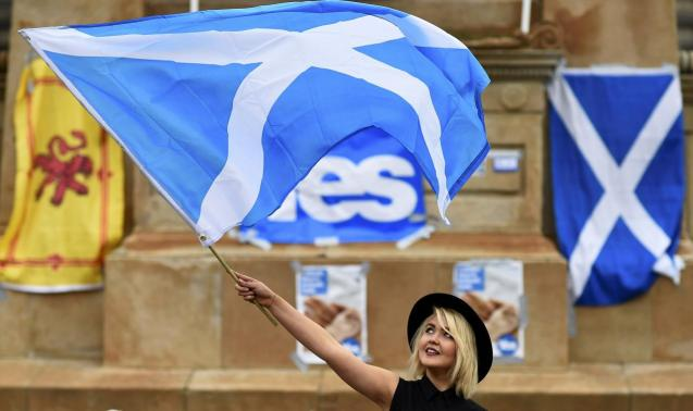 A woman waves a Scottish Saltire