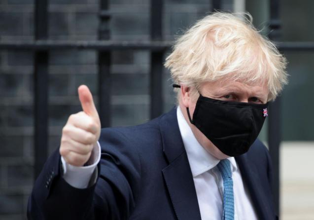 Britain's PM Johnson walks outside Downing Street in London