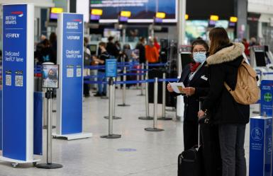 A passenger speaks with a British Airways staff member in the departures area of Terminal 5 at Heathrow Airport in London