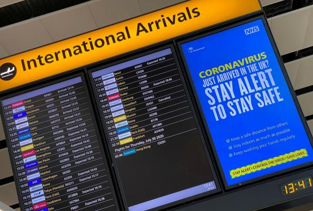 A public health campaign message is displayed on an arrivals information board at Heathrow Airport