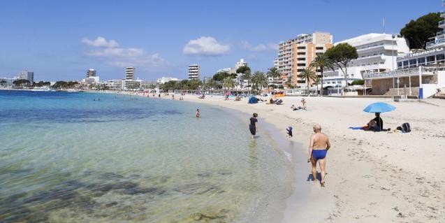 People sunbathe at Magaluf beach in Mallorca