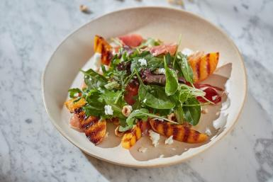 Salad of Iberian ham with grilled peaches, hazelnuts and soft goats cheese dressing.