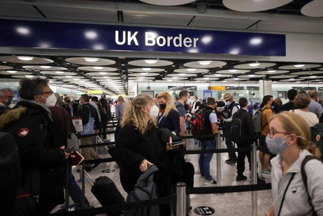 Arriving passengers queue at UK Border Control at the Terminal 5 at Heathrow Airport in London