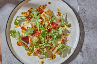 Salad of squid. new potatoes, chorizo and rocket with passion-fruit oil