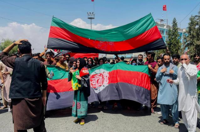 People carry the national flag at a protest held during the Afghan Independence Day in Kabul