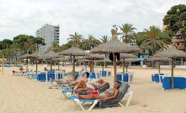 Tourists sunbathing in Palmanova, Mallorca. recent photo.