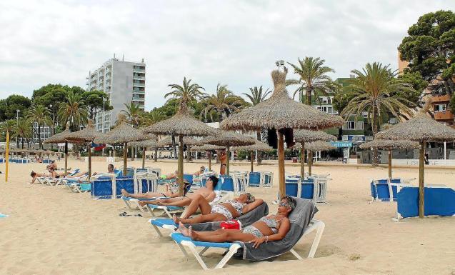 Tourists sunbathing in Palmanova, Mallorca.