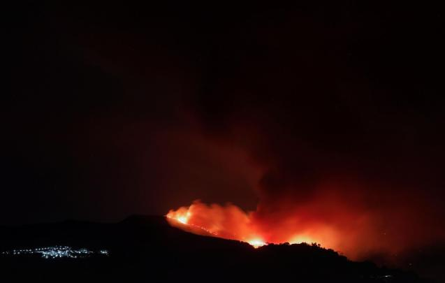 A wildfire is seen from a balcony near the town of Pujerra, which was evacuated, in Cartajima