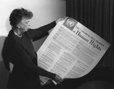 Eleanor Roosevelt, chair of the drafting committee, holding the paper.