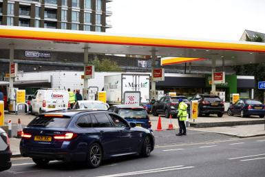Workers guide cars into the forecourt as vehicles queue to refill at a Shell fuel station in London