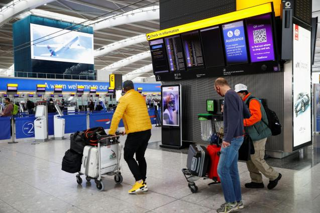 Passengers walk with their bags at the Terminal 5 departures area at Heathrow Airport