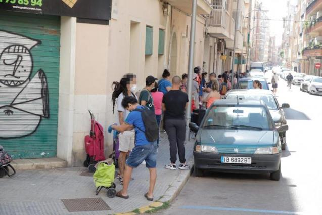 People waiting in line at a food bank in Palma.
